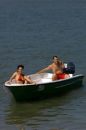 Young couple in a motor-boat relaxing on Bratul Sfantu Gheorghe, Mahmudia, The Danube Delta, Dobrogea, Romania