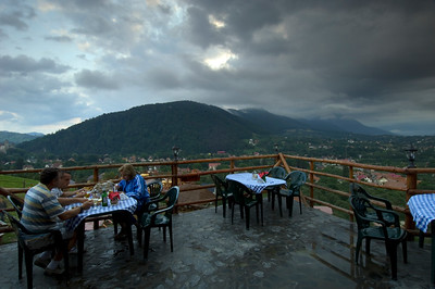 Diners on a restaurant terrace look over Bran village and a Bran Castle, Transylvania, Romania
