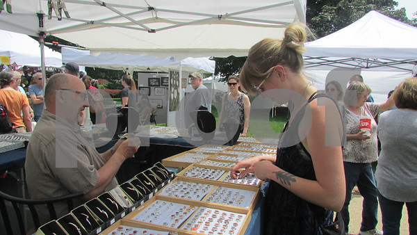 Aimee Barrows for Shaw Media<br /> Sycamore resident Renee Burger tries on rings during the Kishwaukee Valley Art League's 46th annual Northern Illinois Art Show on Sunday, which is held every spring on the DeKalb County Courthouse lawn in Sycamore.