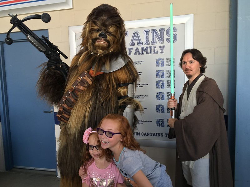 Sisters posing with Chewbacca and a Jedi warrior on Star Wars Night