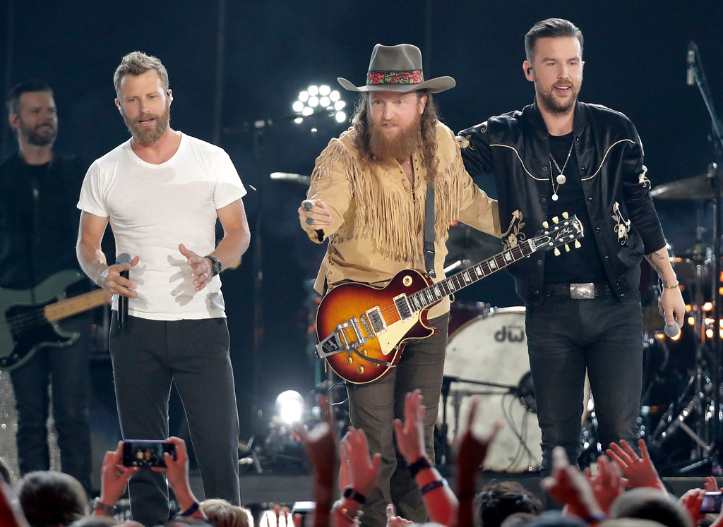 ". Dierks Bentley, from left, John Osborne and T.J. Osborne, of Brothers Osborne, perform ""Burning Man\"" at the CMT Music Awards at the Bridgestone Arena on Wednesday, June 6, 2018, in Nashville, Tenn. (AP Photo/Mark Humphrey)"