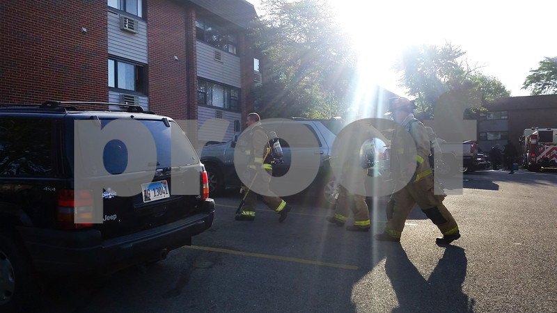 Firefighters walk through the parking lot of Ridgebrook Apartments, 808 Ridge Road.
