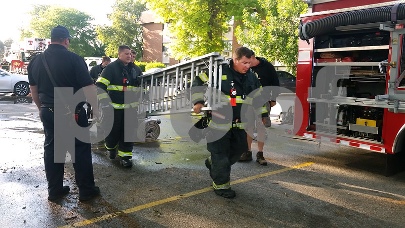 Firefighters bring a ladder back to the engine in the parking lot of Ridgebrook Apartments, 808 Ridge Road, DeKalb, after several residents had to be pulled from their apartments because fire had pinned them in.