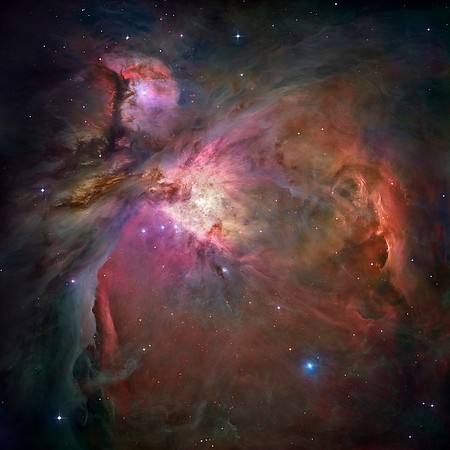 """This dramatic image offers a peek inside a cavern of roiling dust and gas where thousands of stars are forming. The image, taken by the Advanced Camera for Surveys (ACS) aboard NASA/ESA Hubble Space Telescope, represents the sharpest view ever taken of this region, called the Orion Nebula. More than 3,000 stars of various sizes appear in this image. Some of them have never been seen in visible light. These stars reside in a dramatic dust-and-gas landscape of plateaus, mountains, and valleys that are reminiscent of the Grand Canyon. The Orion Nebula is a picture book of star formation, from the massive, young stars that are shaping the nebula to the pillars of dense gas that may be the homes of budding stars. The bright central region is the home of the four heftiest stars in the nebula. The stars are called the Trapezium because they are arranged in a trapezoid pattern. Ultraviolet light unleashed by these stars is carving a cavity in the nebula and disrupting the growth of hundreds of smaller stars. Located near the Trapezium stars are stars still young enough to have disks of material encircling them. These disks are called protoplanetary disks or """"proplyds"""" and are too small to see clearly in this image. The disks are the building blocks of solar systems. The bright glow at upper left is from M43, a small region being shaped by a massive, young star's ultraviolet light. Astronomers call the region a miniature Orion Nebula because only one star is sculpting the landscape. The Orion Nebula has four such stars. Next to M43 are dense, dark pillars of dust and gas that point toward the Trapezium. These pillars are resisting erosion from the Trapezium's intense ultraviolet light. The glowing region on the right reveals arcs and bubbles formed when stellar winds - streams of charged particles ejected from the Trapezium stars - collide with material. The faint red stars near the bottom are the myriad brown dwarfs that Hubble spied for the first time in the nebula in visi"""