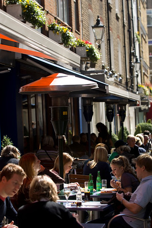 People enjoying a very nice and sunny afternoon in pavement cafes on St Christophers Place, London, W1, United Kingdom