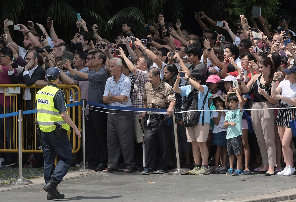 . Curious onlookers wait for the departure of the motorcade of U.S. President Donald Trump from the Istana or Presidential Palace in Singapore on Monday, June 11, 2018, as Trump met Singapore Prime Minister Lee Hsien Loong ahead of the summit with North Korea leader Kim Jong Un. (AP Photo/Joseph Nair)