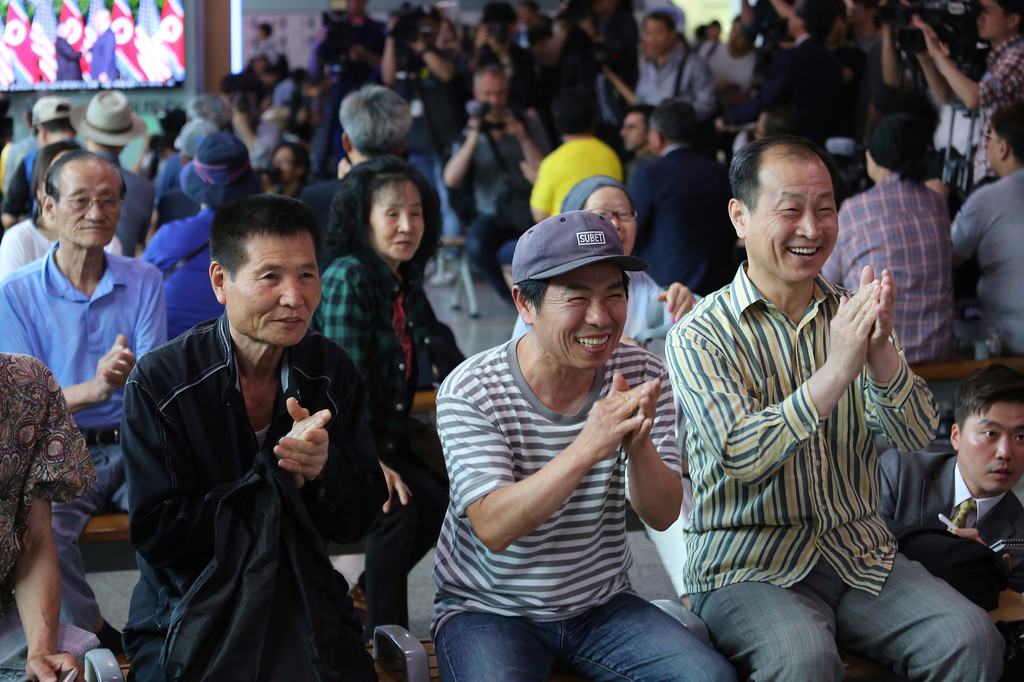 . People celebrate as they watch a TV showing U.S. President Donald Trump meets with North Korean leader Kim Jong Un during a news program at the Seoul Railway Station in Seoul, South Korea, Tuesday, June 12, 2018. (AP Photo/Ahn Young-joon)