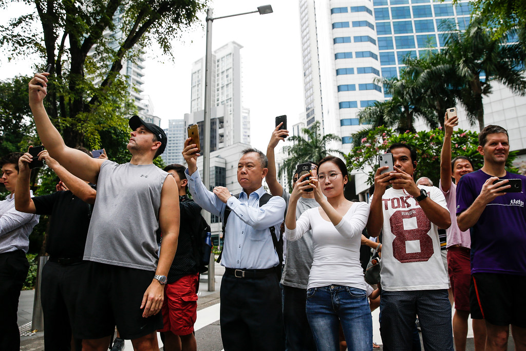 . Members of the public take photos of the motorcade of North Korea leader Kim Jong Un as it leaves the St. Regis Hotel on the way to the Capella Hotel in Singapore, Tuesday, June 12, 2018, where the summit between Kim and U.S. President Donald Trump is scheduled. (AP Photo/Yong Teck Lim)