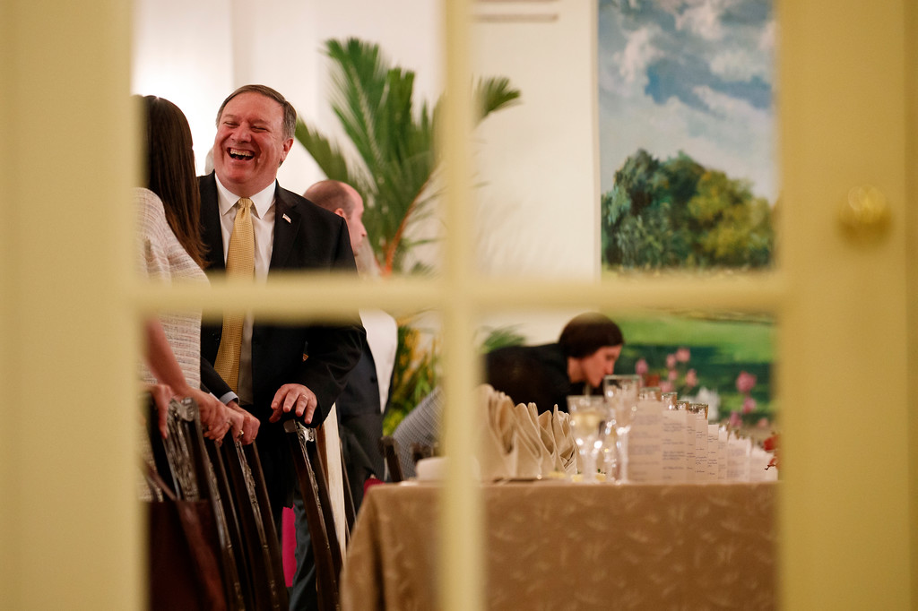 . U.S. Secretary of State Mike Pompeo laughs as he talks with White House press secretary Sarah Huckabee Sanders before a meeting between President Donald Trump and Singapore Prime Minister Lee Hsien Loong, Monday, June 11, 2018, in Singapore. (AP Photo/Evan Vucci)