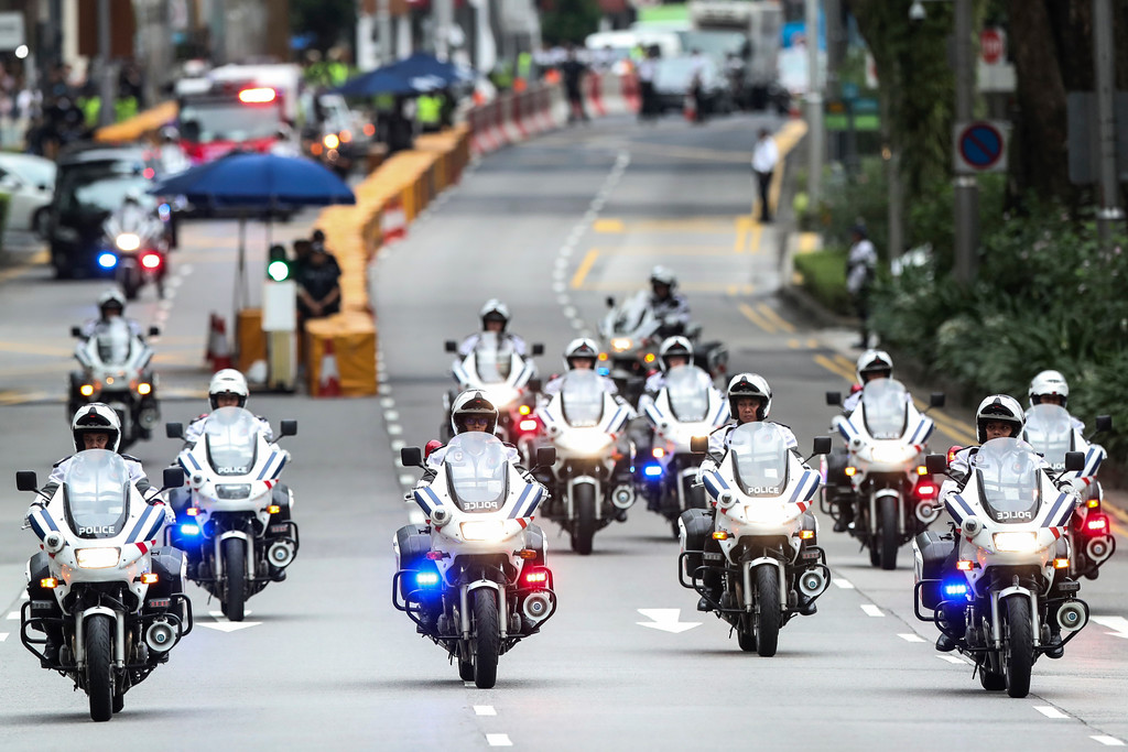 . Police officers lead a motorcade of North Korean leader Kim Jong Un as they leave the St. Regis Hotel on the way to the Capella Hotel in Singapore, Tuesday, June 12, 2018, where the summit between Kim and U.S. President Donald Trump will take place. (AP Photo/Yong Teck Lim)