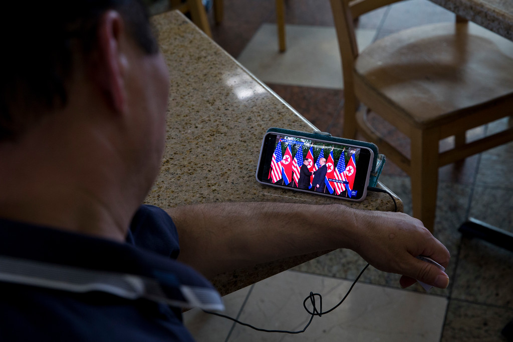 . Richard Jang, 50, watches coverage of U.S. President Donald Trump\'s meeting with North Korean leader Kim Jong Un on his smartphone Monday, June 11, 2018, in Los Angeles. (AP Photo/Jae C. Hong)