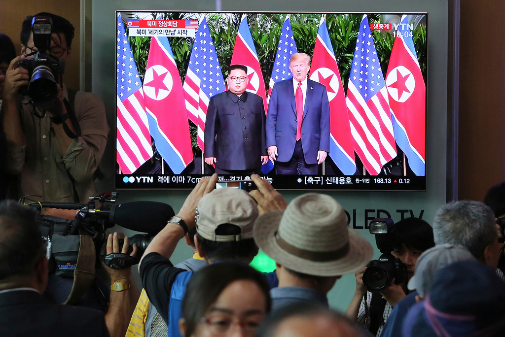 . People watch a TV screen showing U.S. President Donald Trump, right, meeting with North Korean leader Kim Jong Un in Singapore during a news program at the Seoul Railway Station in Seoul, South Korea, Tuesday, June 12, 2018. (AP Photo/Ahn Young-joon)