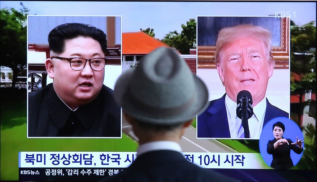 ". A man watches a TV screen showing file footage of U.S. President Donald Trump, right, and North Korean leader Kim Jong Un during a news program at the Seoul Railway Station in Seoul, South Korea, Monday, June 11, 2018.  Final preparations are underway in Singapore for Tuesday\'s historic summit between President Trump and North Korean leader Kim, including a plan for the leaders to kick things off by meeting with only their translators present, a U.S. official said.  The signs read: "" Summit between the United States and North Korea.\"" (AP Photo/Ahn Young-joon)"