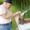 Jonathan Tressler - The News-Herald. Longtime beekeeper Dave Paterson works its built-in bellows to stoke the smoker he uses to calm the honeybees he keeps in numerous hives in his Hambden Township back yard. Each hive contains up to 50,000 bees, Paterson said.