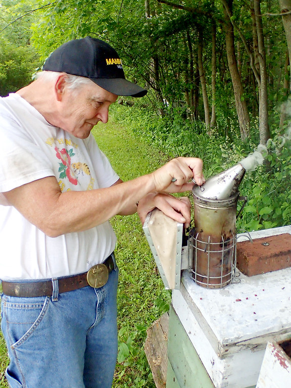 . Jonathan Tressler - The News-Herald. Longtime beekeeper Dave Paterson works its built-in bellows to stoke the smoker he uses to calm the honeybees he keeps in numerous hives in his Hambden Township back yard. Each hive contains up to 50,000 bees, Paterson said.