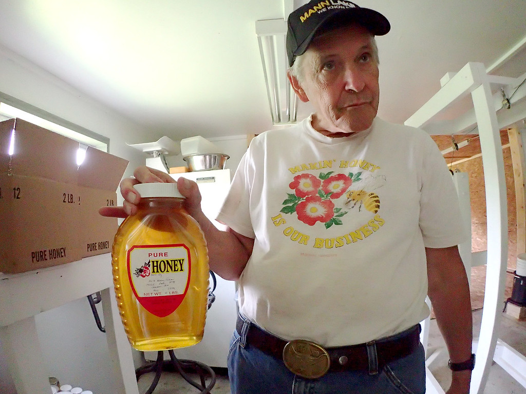 . Jonathan Tressler - The News-Herald. Dave Paterson, a 28-year veteran beekeeper, holds up a four-pound jar of honey produced at the Hambden Township property he and wive, Alnita, call home. Paterson said it�s unlikely much of the honey billed as �pure clover� is actually pure clover because bees collect nectar from so many different kinds of flowering plants. Therefore, he said, the stuff he and Alnita produce is labeled �wildflower honey.�