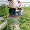 Jonathan Tressler - The News-Herald. Hambden Township resident Dave Paterson, a veteran beekeeper, works the bellows on the smoker he uses to calm the hives as he prepares to look in on one in this June 7 photo.