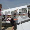 Instructor Larry Cabeen watches Clara Colness, 7, of DeKalb, get into the plane during the Young Eagles program Sunday morning at DeKalb Taylor Municipal Airport.