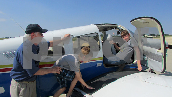 Instructor Wes Lundsberg helps Michael Reynolds, 10, on to the plane as his brother, Thomas, 12, looks on.
