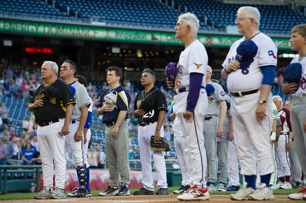 . Members of the Democratic and Republican baseball teams stand for the national anthem to start the 57th Congressional Baseball Game at National\'s Park in Washington, Thursday, June 14, 2018. On June 14, 2017, some Congressional members were victims of a shooting at the baseball field they were practicing on in Alexandria, Va. (AP Photo/Cliff Owen)