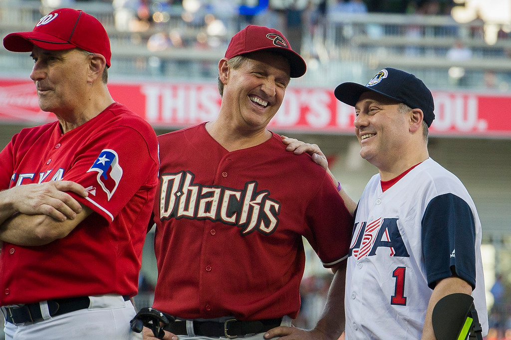 . Rep. Jeff Flake, R-Ariz., center, talks with Rep. Steve Scalise, R- La., at the start of the 57th Congressional Baseball Game at National\'s Park in Washington, Thursday, June 14, 2018. Scalise, the House majority whip who was shot at a Republican baseball practice a year ago, fielded a ground ball and threw out the first batter of the annual congressional baseball game Thursday. (AP Photo/Cliff Owen)