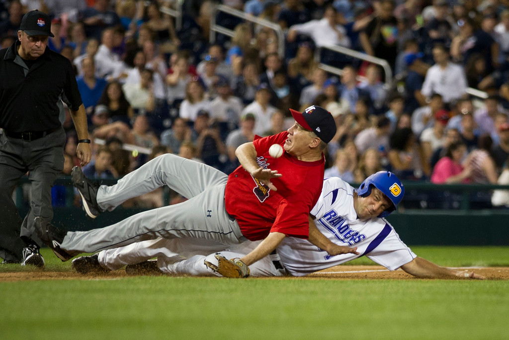 . Rep. Tim Ryan, right, D-Ohio, collides with Rep. Trent Kelly, R-Miss., as Ryan steals third base during the 57th Congressional Baseball Game at National\'s Park in Washington, Thursday, June 14, 2018. Members of Congress played their annual baseball game Thursday night - a year after some Republican players and others were wounded in a shooting spree at a team practice in Virginia. (AP Photo/Cliff Owen)