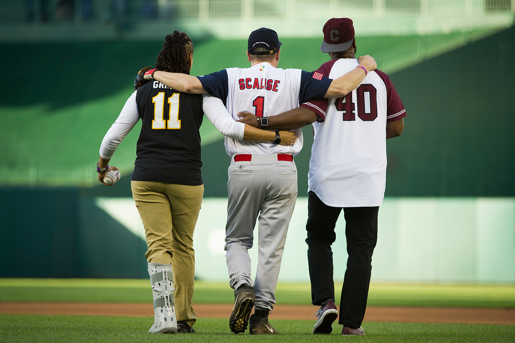 . Capitol Police Special Agents Crystal Griner, left, and David Bailey, right, assist U.S. Rep. Steve Scalise to his position at second base at the start of the 57th Congressional Baseball Game at National\'s Park in Washington, Thursday, June 14, 2018. On June 14, 2017, Scalise was wounded in the leg when he and other Congressional members were the victims of a shooting at the baseball field they were practicing on in Alexandria, Va. (AP Photo/Cliff Owen)