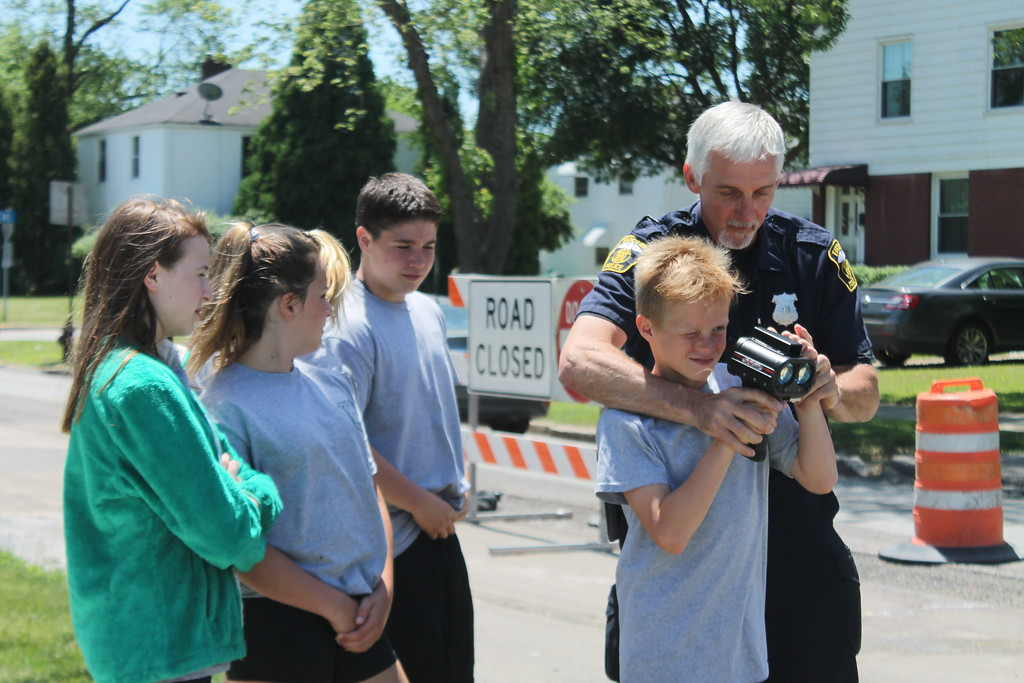 . Euclid police Officer Tony Brentar  explains to the cadets enrolled in the department\'s Jr. Police Academy about traffic stops shows Owen Pesek, 10 how to use radar to  tell how fast a vehicle is going. Kristi Garabrandt - The News-Herald