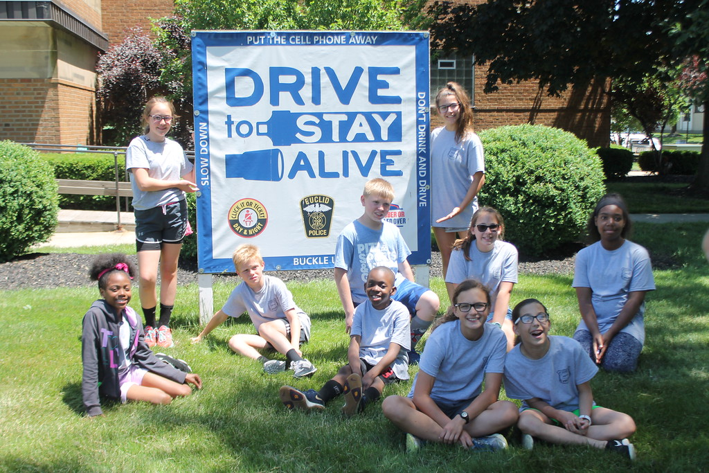 . Cadets  in Euclid\'s  Police Department\'s Jr. Police Academy stand around a sign in front of the Euclid Police Department  cautioning people to drive safe. Kristi Garabrandt - The News Herald