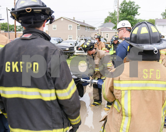 Zach Rissman a senior at Sycamore high school uses the Jaws of Life during Kishwaukee Education Consortium program held on June 19 in Rochelle while others look on with the guided help of Josh Lewis who is from the Rochelle Fire department. (white hard hat)