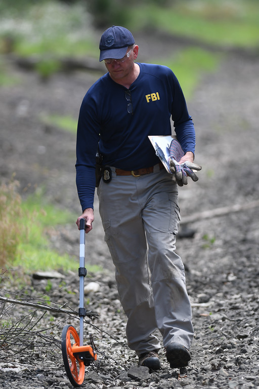 . Eric Bonzar � The Morning Journal <br> An FBI agent measures the distance from a wooded area near Mussey Avenue in Elyria, out to the roadway, June 21, 2017. The FBI�along with Middleburg Heights and Elyria police�searched the area, in connection with the March 2015 disappearance of Middleburg Heights resident Tierra Bryant, who was 19 years old at the time she went missing.