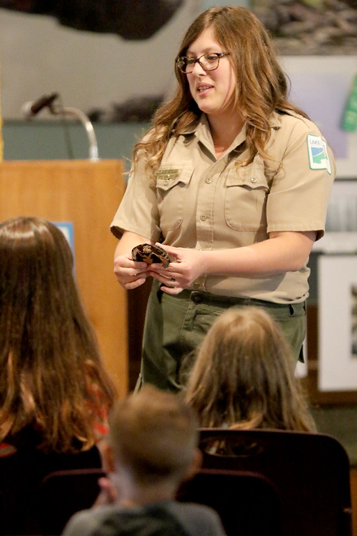 . Jonathan Tressler � The News-Herald <br> Kirsten Bull, a part-time Lake Metroparks wildlife education specialist, introduces Dot the spotted turtle to a family-filled audience inside the nature center at Penitentiary Glen in Kirtland June 23 as part of the program offerings during the Great American Backyard Campout event held there June 22-24.