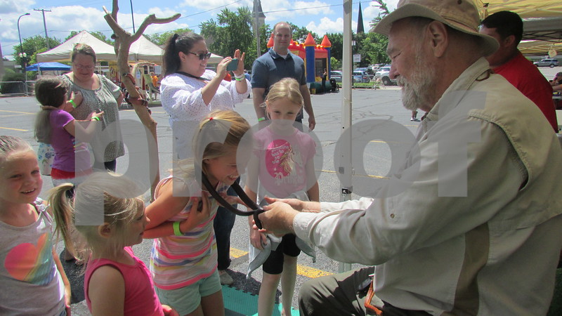"""Aimee Barrows – for Shaw Media<br /> Madison Corneille, 9, holds a snake around her neck during the annual """"Rockin' for the Reptiles"""" fundraiser in downtown Sycamore."""