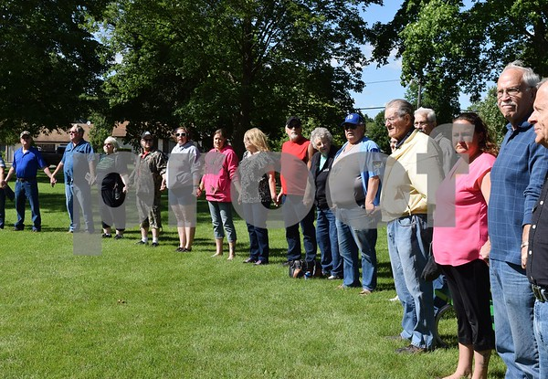 "Katrina J.E. Milton - kmilton@shawmedia.com<br /> Attendees of Les Bellah's celebration of life, hold hands in a circle and sing Lee Greenwood's ""God Bless the USA,"" Bellah's favorite song which is played every year during Kirkland's Memorial Day service."