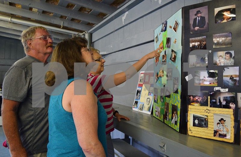 Former neighbors of longtime Kirkland Village President Les Bellah look at pictures during his celebration of life gathering Saturday at Franklin Township Park in Kirkland. From left, Herb Johnson and Carol Johnson of Kirkland and Kathy Madsen of Rochelle.