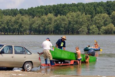 Europe, Romania, The Danube Delta, Mahmudia, local men pull a boat into a river
