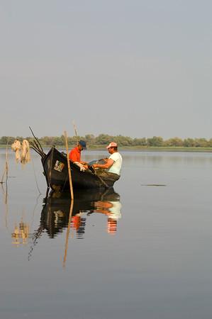 Europe, Romania, The Danube Delta, Lake Uzlina , fishermen in a boat setting nets