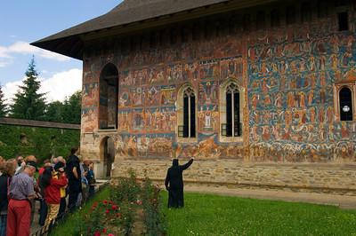 Europe, Romania, Moldavia ,Bucovina, Moldovita Monastery, resident nun explains frescoes to visitors