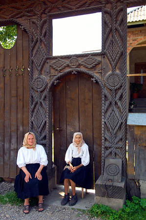Europe, Romania, Maramures, two women sitting by wooden gate , typical for Maramures region