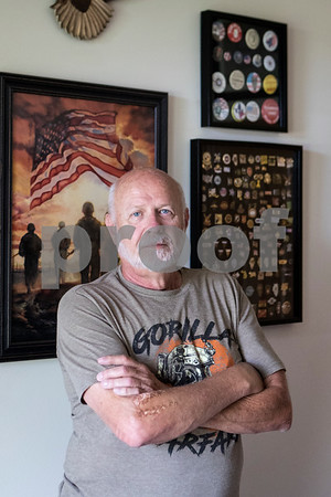 Sam Buckner for Shaw Media.<br /> Herb Holderman, a Vietnam war veteran, poses in front of  military art and his collection of hat pins at his home on July 2, 2017.