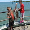 Richard Payerchin - The Morning Journal <br> Hayden Foutz, 8, of Avon Lake, left, holds up a sheephead he caught at the Miller Road Park Pier on July 2, 2016. Foutz participated in a youth fishing derby held by the Avon Lake Parks and Recreation Department in conjunction with the fourth annual Hooks for Hunger Walleye Tournament, a fundraiser for Community Resource Services. The agency seeks to alleviate poverty in Avon Lake and Avon.