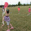Richard Payerchin - The Morning Journal <br> Haley Bacskay, 9, of Elyria, at left in foreground, holds a kite as her sister, Haiden, 6, in background at right, prepares to get it airborne as part of the inaugural Over the Rainbow Kite Festival on July 2. Victory Park Ohio hosted the event as a fundraiser for Rainbow Babies & Children's Hospital. In the background center is Hannah, 6, twin sister of Haiden and younger sister of Haley. They attended with their mother, Stephanie Bacskay.