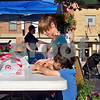 Briar Trebee, 9, helps Eric Mitchell, 3, build a pretzel necklace at the Sycamore Kiwanis Craft Beer and Brat Fest Saturday.