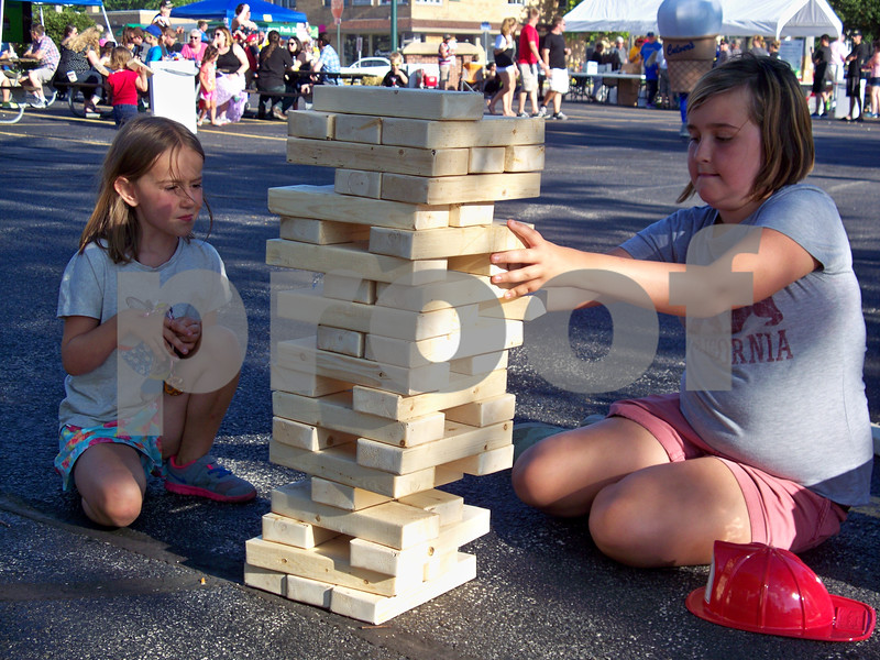 """Seven year-old Reid Walzer (left) and sister Ella Walzer, 12, enjoy a game of Jenga at the festival after shooting water with the fire department. The girls said they enjoyed the event, and Reid liked sampling the pineapple bratwurst. """"She loves pineapple,"""" said Ella."""