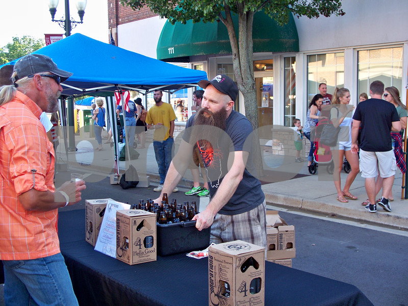 Assistant Brewer Chris Duffy (right) talks with an attendee about his company's craft brews. His company came from Freeport to participate in the event.