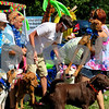 Mid Day Play Pet Services employees Linda Race (from left), Amy Lundeen, float helper Dylan Woods and owner Lanette Yingling get the dogs in place to take a photo Saturday before the Sandwich Fourth of July parade.