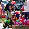 Jonathan Tressler — The News-Herald <br> Five-year-old Jase Palmer of Hambden township, works to negotiate a crosswalk between flower beds on Short Court Street in Chardon July 4 following the bike parade during the city's Old Glory Day event. He's being helped by grandmother, Mary Hedrick, left, grandfather, Harold Hedrick and mom, Sharon Palmer.