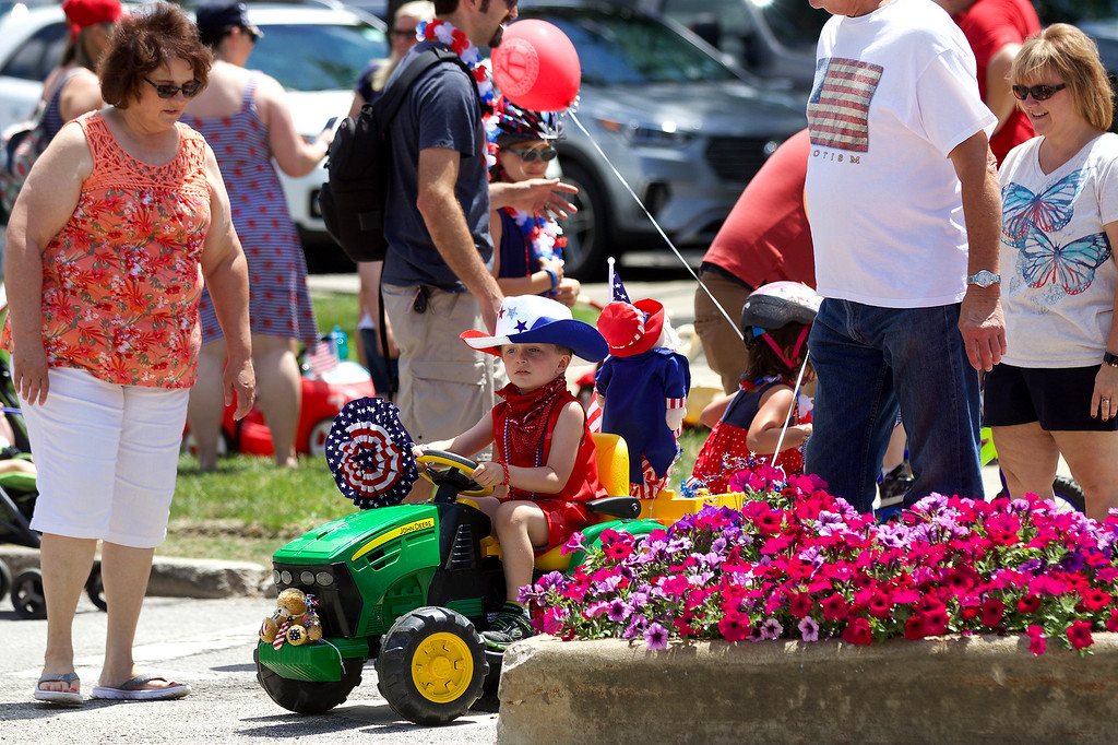 . Jonathan Tressler � The News-Herald <br> Five-year-old Jase Palmer of Hambden township, works to negotiate a crosswalk between flower beds on Short Court Street in Chardon July 4 following the bike parade during the city\'s Old Glory Day event. He\'s being helped by grandmother, Mary Hedrick, left, grandfather, Harold Hedrick and mom, Sharon Palmer.