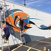 Chad Felton — The News-Herald <br> Roy Reid, left, and Bob Peck work on a mural on the side of Sammich on E. 185th Street. The public art project, approved by Euclid's Architectural Review Board, is an abstract expression mixed with spray paint and latex paint.