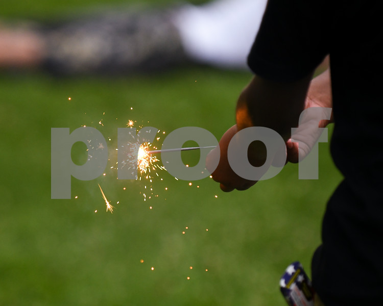 A young boy plays with a sparkler before the firework display at Hopkins Park on July 4th.